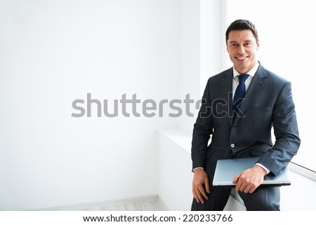 Man in suit with laptop - stock photo