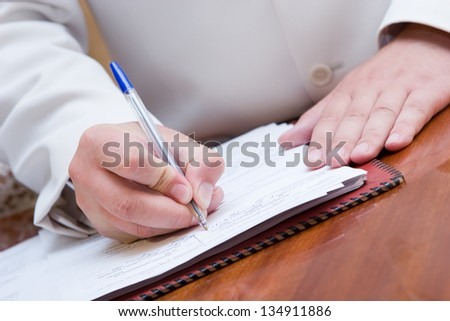 man in suite signing paper - stock photo