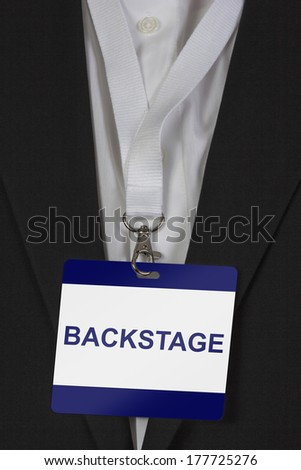 man in suite wearing a Backstage pass arround his neck - stock photo