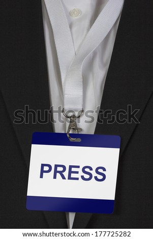 man in suite wearing a Press pass arround his neck - stock photo
