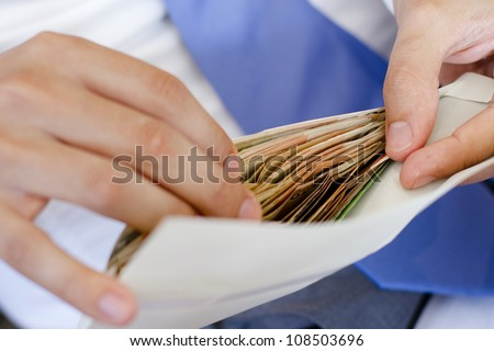 Man in suits is counting how much money in an envelope - stock photo