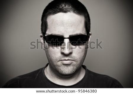Man in sunglasses looks threatening - stock photo