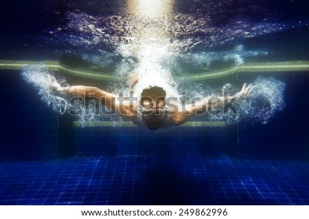 man in sunglasses underwater dives under water in the pool - stock photo
