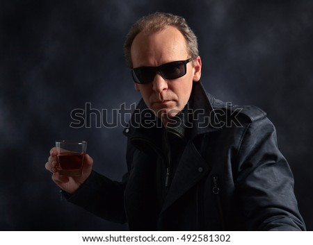 man in sunglasses with glass of whiskey