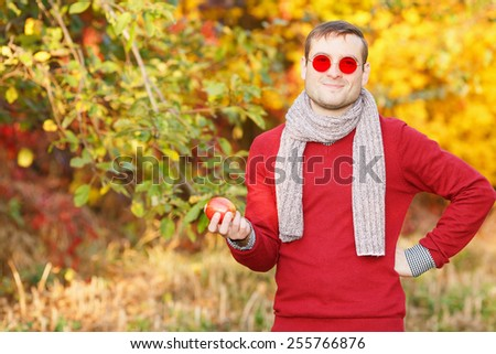 Man in sunglasses with red glasses. Ordinary people. A young man with a beautiful smile in a city park. A walk in the fresh air on a warm day. Warm clothing red warms. Keep red apple in hands. - stock photo