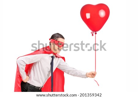 Man in superhero costume holding a balloon isolated on white background - stock photo