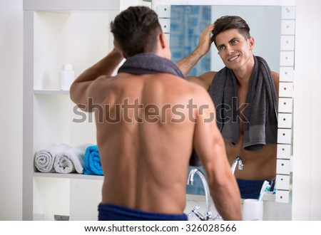 Man in the bathroom looking in a mirror and fixing his hair. - stock photo
