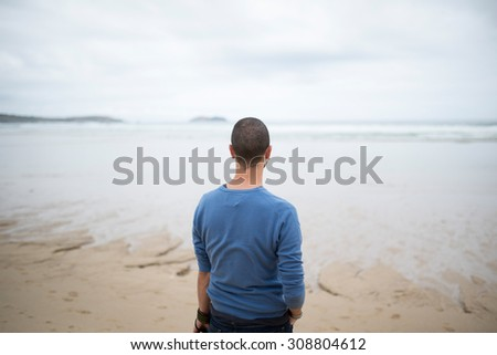 Man in the beach looking to the sea, rear view. - stock photo