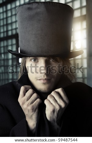Man in the black coat and top hat. Artistic colors and grain added - stock photo