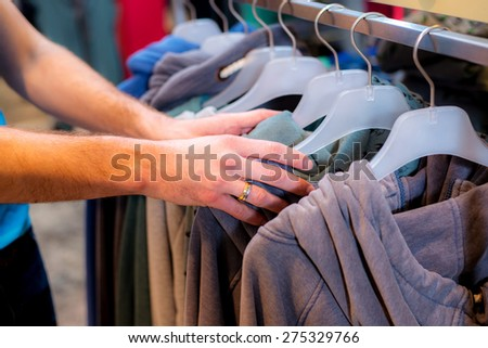 man in the clothes shop looking for outfit - stock photo