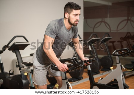 Man In The Gym - Exercising His Legs Doing Cardio Training On Bicycle - stock photo
