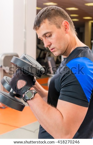 man in the gym with two heavy dumbbells