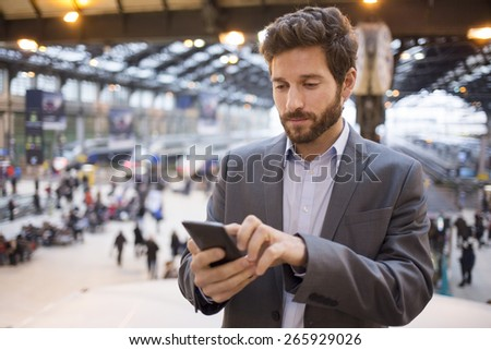 Man in the hall station. Typing text message  on mobile phone - stock photo