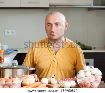 Man in the kitchen who prepare soup - stock photo