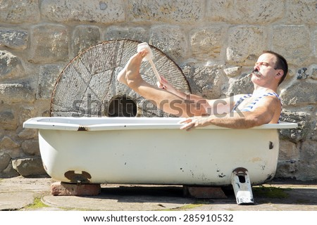 man in the outdoor bathtub washes his leg - stock photo