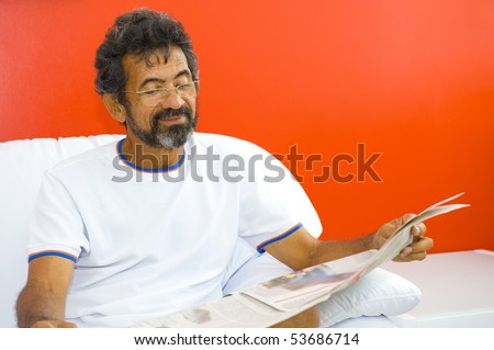 Man in the sofa, reading news paper
