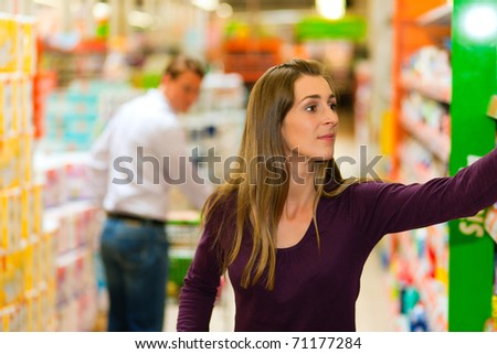 Man in the supermarket looking after a girl he just met shopping there, he is ready to flirt a bit - stock photo