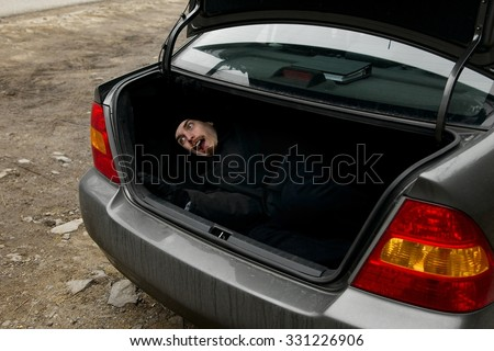 Man in the trunk of a car - stock photo