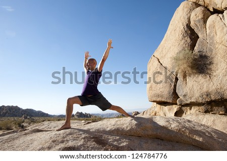 Man in the yoga pose warrior one outdoors. - stock photo