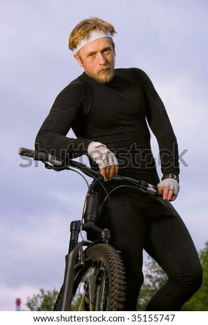man in tracksuit standing and holding his bicycle