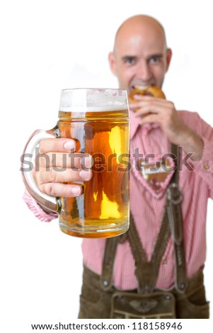 man in traditional bavarian garb with beer eats a pretzel - stock photo