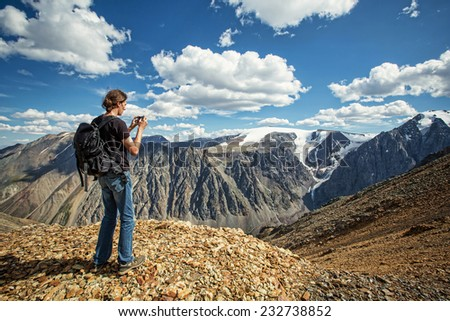 Man in travel in the mountains make photo on mobile phone - stock photo