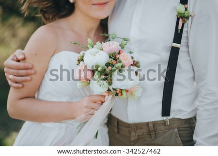 man in trousers and a shirt, and a girl in a wedding dress standing on the grass in the field, and are holding a bouquet of flowers and greenery