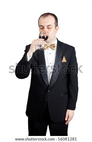 Man in tuxedo drinking red wine from the glass - stock photo