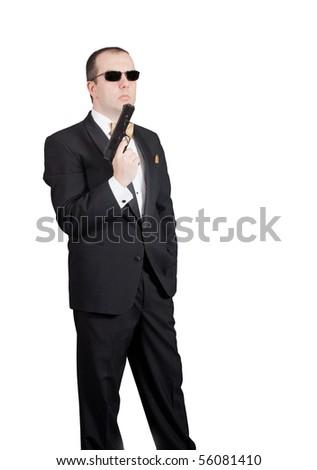 Man in tuxedo looking at his gun - stock photo