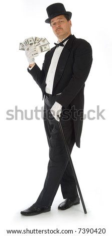 Man in tuxedo, top hat and cane fanning himself with stacks of money - stock photo