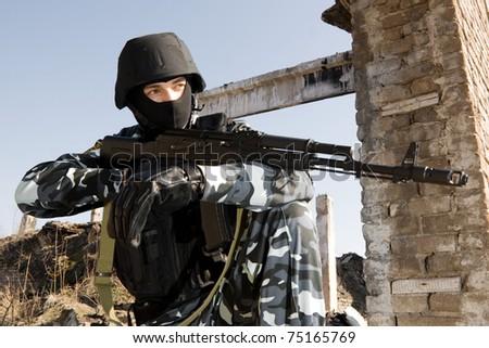 Man in uniform and full combat ammunition holding the gun - stock photo
