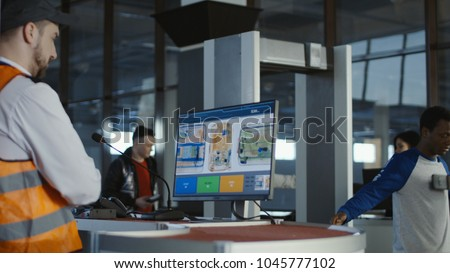 Man in uniform watching monitor with x-ray of baggage checking passengers in airport.