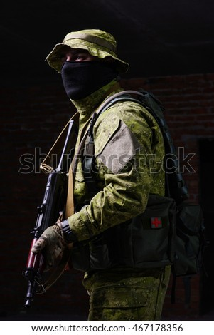 Man in uniform with mask and gun in hands on dark background/Man with gun