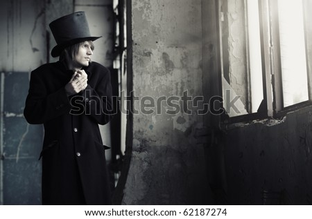 Man in vintage black coat and top hat indoors looking to the window. Artistc colors added - stock photo