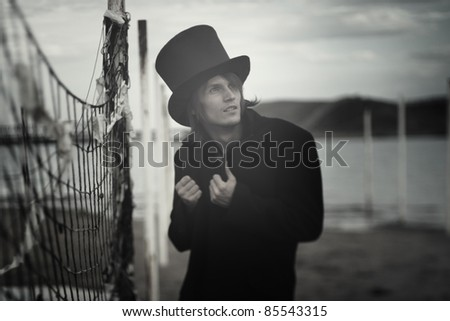 Man in vintage black coat and top hat outdoors. Artistic colors added. Natural light and darkness. Shallow depth of field added for artistic view - stock photo
