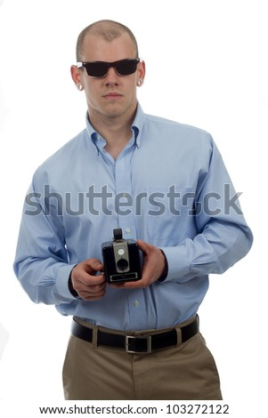 man in vintage sunglasses poses with retro camera - stock photo