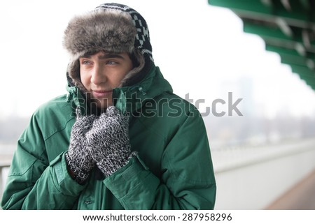 Man in warm clothing shivering outdoors - stock photo