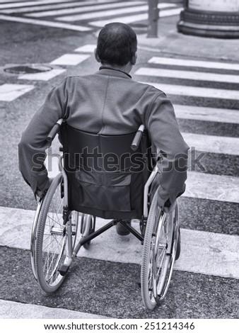 Man in wheelchair crossing a zebra - stock photo