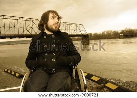 Man in wheelchair in front of river.  Shot in Harrisburg, PA. - stock photo