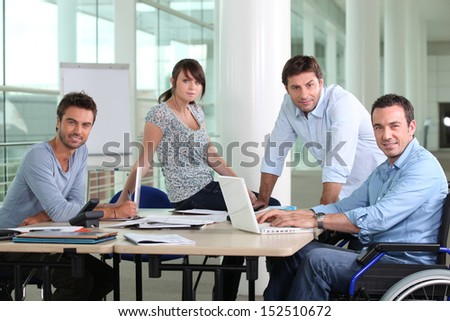 Man in wheelchair sat at desk with colleagues - stock photo