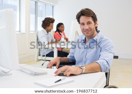 Man in wheelchair works hard looks at the camera in the office