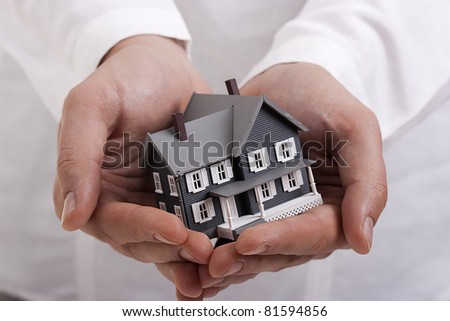 Man in white holding a model of a house in his hands. - stock photo