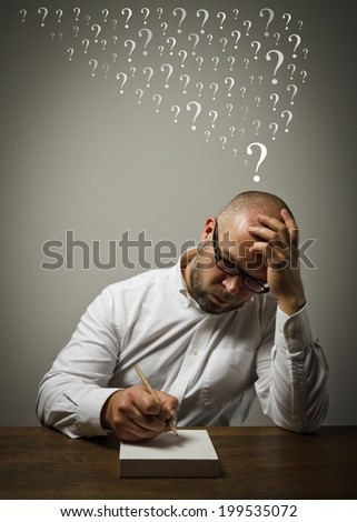 Man in white is sitting at the table and is ready to write something. Question marks. - stock photo