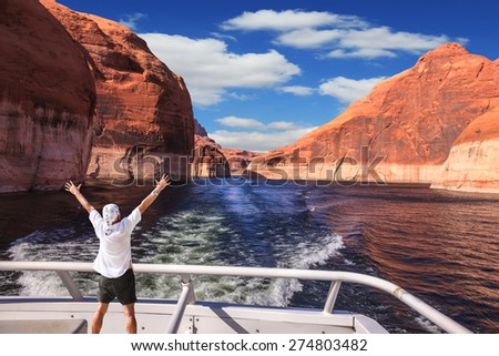 Man in  white shirt on the stern boat fascinated by nature. Artificial lake Powell on the Colorado River, USA. The lake is surrounded by picturesque beaches of the orange sandstone - stock photo