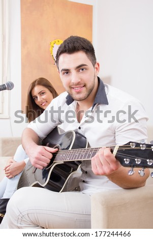 man in white shirt playing guitar and singing with cute girl beside him