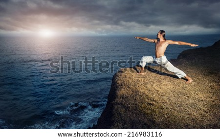 Man in white trousers doing Yoga warrior pose on the cliff near the ocean in Kerala, India