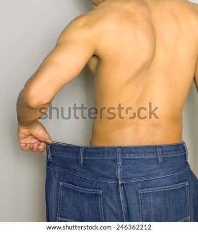 man in wide trousers losing weight - stock photo