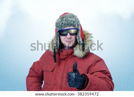 Man in winter clothes and sunglasses it shows thumb. Polar explorer - stock photo