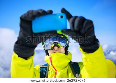 Man in winter clothes taking a selfie with skis - stock photo