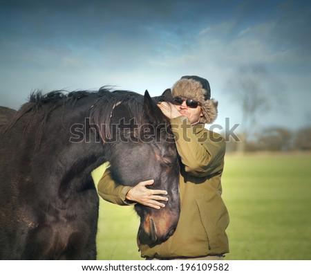 Man in winter hat hugging black old horse - stock photo